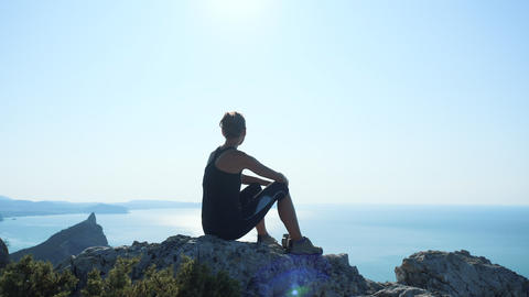 Silhouette of a happy hiker woman sitting and relaxing on the summit and Footage