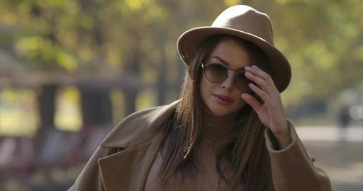 Portrait of young cute European girl in elegant hat taking off sunglasses and Footage