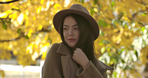 Portrait of attractive European girl in brown hat standing on the background of Footage
