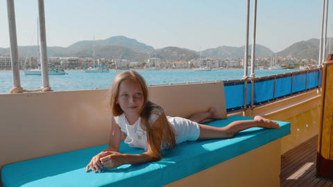 Carefree girl relaxing on couch sailing boat on sea cruise on mountain landscape Footage
