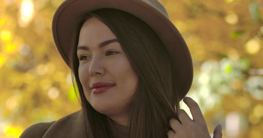 Close-up portrait of attractive European girl in brown hat standing on the Footage