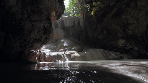Cave waterfall in a rocky wall with water droping and flowing against sunlight Footage