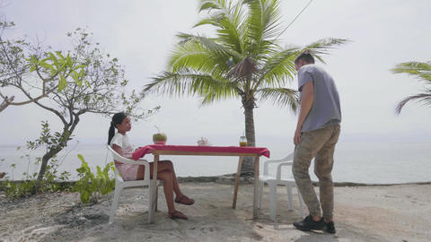 Young man and woman relaxing on the beach and drinking juice Footage