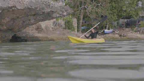A slim woman enjoys kayaking in the coastal beach resort on holiday Live Action