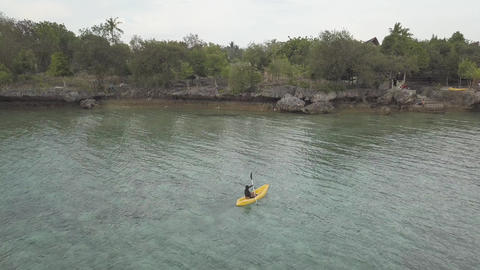 Drone footage: Female tourist kayaking in the peaceful sea at a tropical resort Live Action