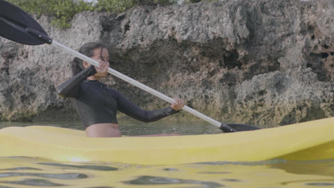 A young woman kayaking in the sea. Active lifestyle and adventure concept Live Action