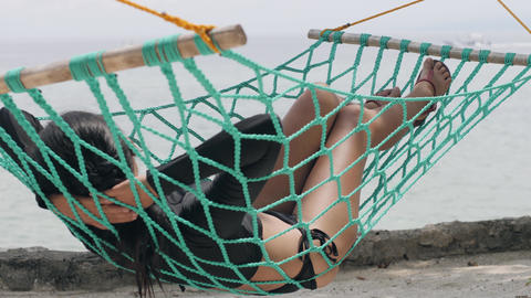 Tan skinned woman lying on a green hammock in front of calm sea Footage