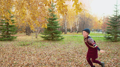 Carefree girl throwing yellow maple bouquet in autumn park. Smiling girl Footage