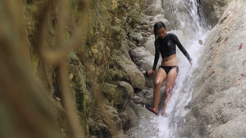Woman with slender body relaxing under topical waterfalls in the forest Footage