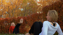 Sport woman training stretching exercise on carpet in autumn park. Yoga woman Footage