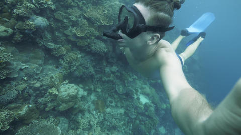 Freediving: self-portrait of a man snorkeling in the ocean rich in corals Live Action