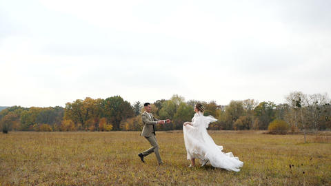 Young attractive Bride and Groom run to each other in Slow motion along an Live Action