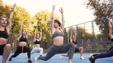 Likable young fitness women doing yoga exercises with raised hands on the Footage