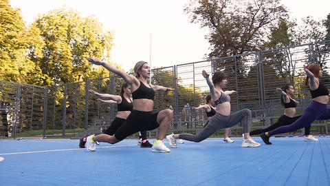 Seven young slender women doing stretching exercises on the sportground in the Footage
