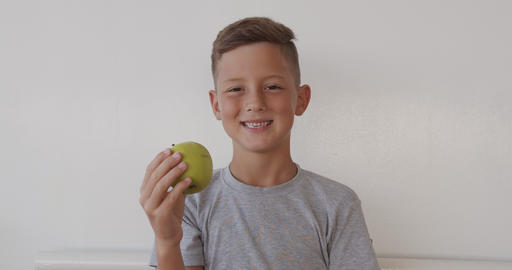 Close up portrait boy eating tasty green apple and looking at camera Footage