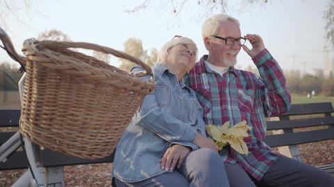 Side view of Caucasian retired man and woman sitting on the bench in sunlight Footage
