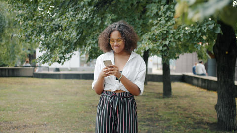 Portrait of cheerful African American girl using smartphone outdoors in city Footage