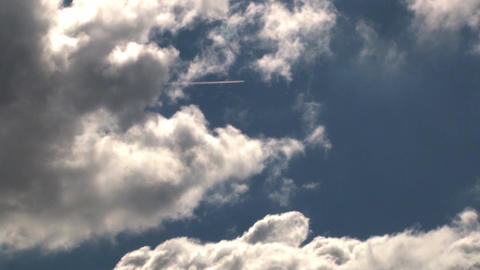 Jumbo jet coming out speed between white and fluffy clouds that go with speed in Live Action