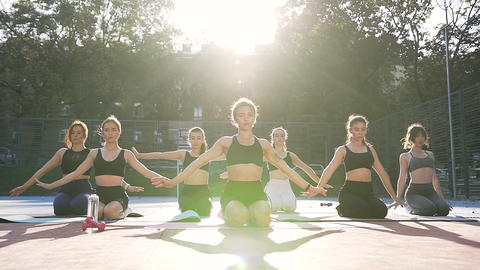Front view of female fitness team which kneeing and doing relaxing exercises Footage