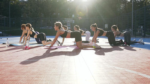 Seven good-looking athletic girls in sportswear lying on mats and doing relaxing Footage