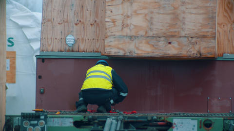 Cargo shipping - men working on the construction site - unhook the cargo from Live Action