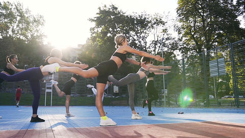 Side view of seven sporty good-looking women which doing balance exercises on Footage
