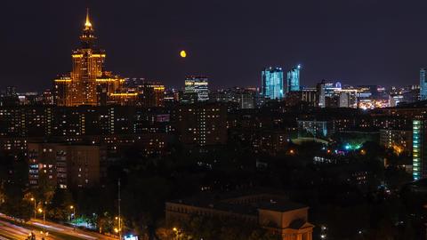 Timelapse architecture night city on dark sky landscape. Night illumination in modern city. Moon Live Action