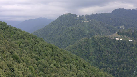 Aerial view moving cable car cabin among forest trees in mountain. Cable car moving up on rope way Live Action