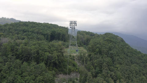 Aerial view moving cable car cabin among summer forest trees in cloudy mountain. Cable car moving on Live Action