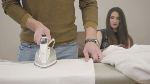 Close-up of adult male Caucasian hands ironing as brunette woman sitting at the Footage