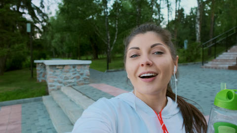 Attractive young woman in a sports sweater takes a selfie on a smartphone before Footage