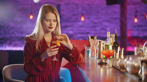 Gorgeous young woman sitting by the bartender stand - taking the drink from the Live Action