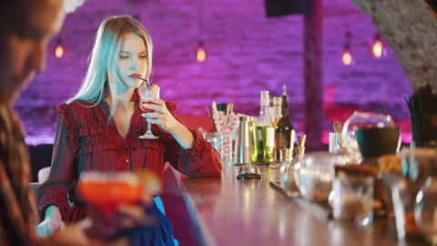 Gorgeous blonde young woman sitting by the bartender stand - drinking a beverage Live Action