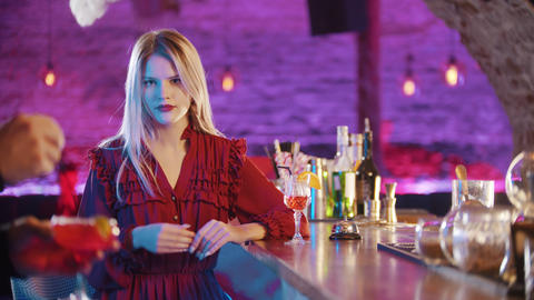 Gorgeous blonde young woman sitting by the bartender stand and cheking out her Live Action