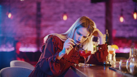 Gorgeous bored young woman sitting by the bartender stand and stirs the drink Live Action