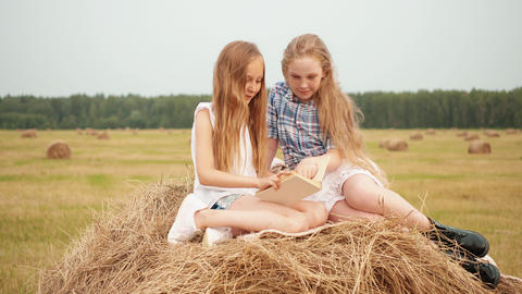 Cute cheerful girls sitting on haystack and reading book Footage