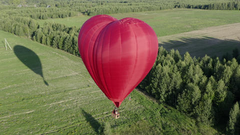 Red air love balloon in heart shape flying over green field at sunny day. Drone view aerostat with Footage