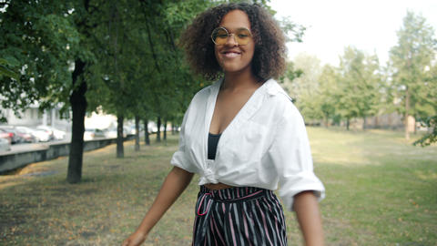 Slow motion of beautiful African American lady walking outdoors in park turning Footage