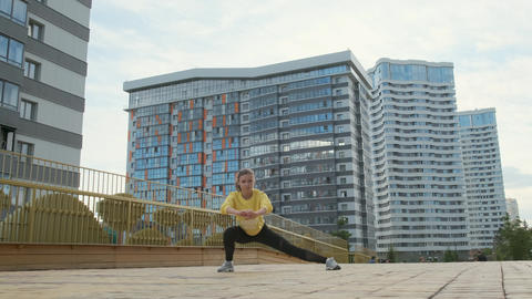 RUSSIA, NOVOSIBIRSK - 06-10-2019: Young sporty woman exercises in an urban Live Action