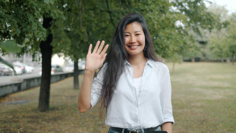Slow motion portrait of Asian girl waving hand smiling outdoors in urban park Footage