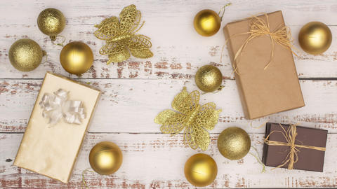 Gold Christmas decoration with presents appear on wooden background - Stop motion Animation