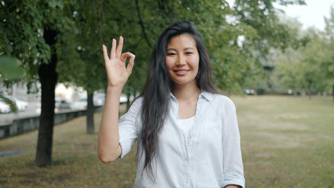 Beautiful Asian woman showing OK hand gesture outside in city park smiling alone Footage