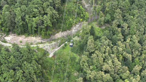 Aerial shooting from drone cable car moving up on ropeway in green mountain. Drone view from above Live Action