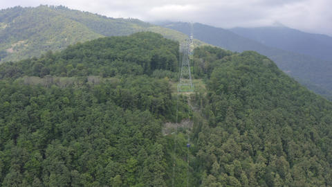 Cable car cabin moving on rope way in green mountain view from drone above. Cable car on high forest Live Action