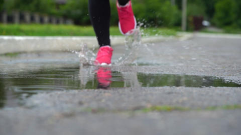 Legs of a runner in sneakers. Sports woman jogging outdoors, stepping into muddy Archivo