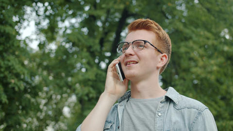 Attractive businessman in glasses talking on mobile phone outdoors in city park Footage