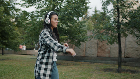 Slow motion of Asian lady dancing outdoors in city park wearing headphones Footage