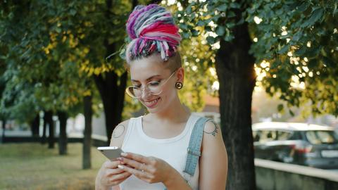 Stylish lady using smart phone outside in park smiling enjoying social media Footage