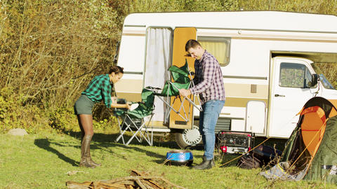 Relaxed couple setting up their camping chairs Footage