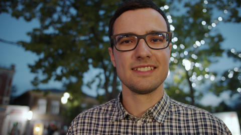 Portrait of attractive businessman in glasses looking at camera in city at night Footage